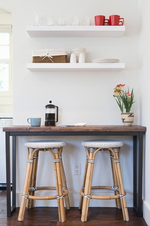 Kitchenette features a wood and iron bar table lined with French bistro stools, Serena & Lily Riviera Stools, placed under stacked white floating shelves. Description from decorpad.com. I searched for this on bing.com/images