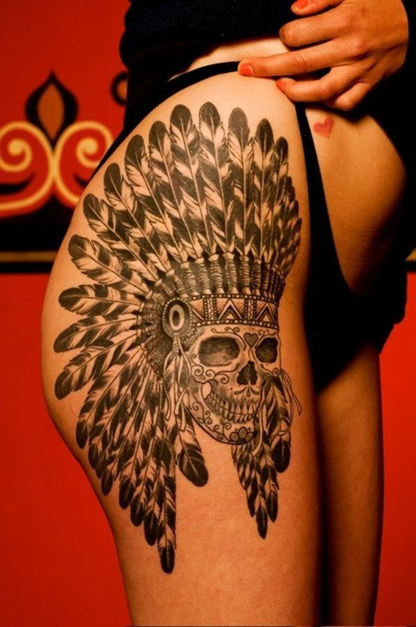 A thigh tattoo with a skull portrait. The feather made headdress reminds you of native American Indians.
