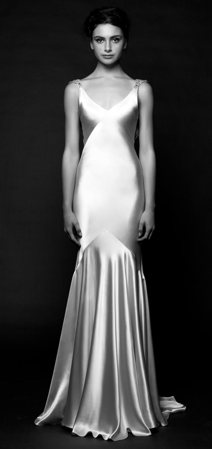 Fluid silk charmeuse and minimalist architectural seams sculpt Daxa's bewitching shape. Art Deco-inspired crystal details at the shoulder frame a plunging back cowl and V-neckline.  Gown by Sarah Janks