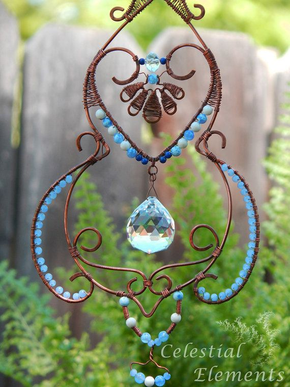Sun-catcher, copper wire is used for frame and wire weaving, blue gemstones, and crystals are used for embellishment, has symbolic meaning