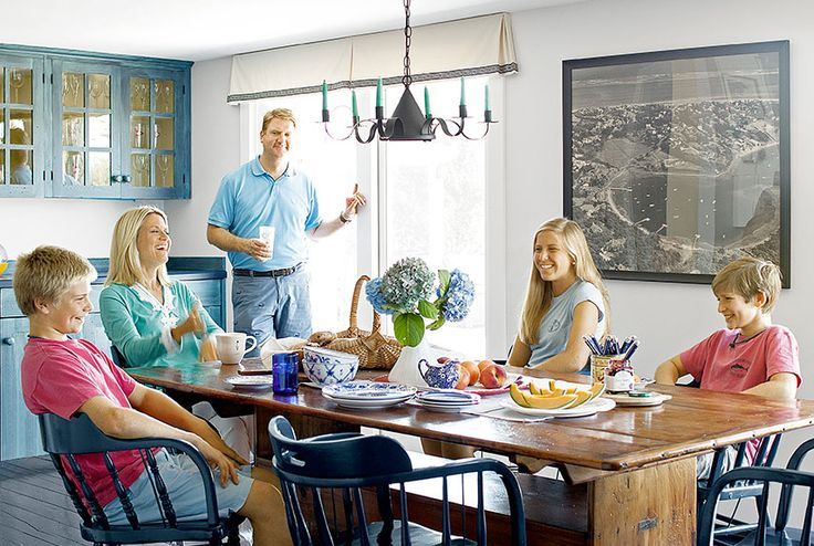 Martha MacCallum and her husband, Dan, gather in the dining area with their children (from left), Reed, Elizabeth, and Harry. The aerial photograph of the neighborhood was taken by Kelsey-Kennard in the 1960s. The dining chairs and flooring are painted Hale Navy by Benjamin Moore.