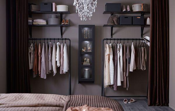 Åpen garderobe bestående av hengende oppbevaring, åpne hyller og et vitrineskap fullt av klær og esker.