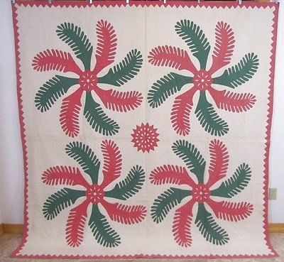 A lovely princess feather applique quilt in a 4 block pattern and framed with applique dogtooth.  Has reverse applique work also. Executed in solid green and pink.  Measurement: 87 x 84 inches  Hand quilted 10 stitches per inch.  Edges meet and hand sewn. Batting is thin. Applique hand sewn.  Crisp, never used or washed.  Has scattered age spotting in places. On back folds, age spotting and some soiling.  The quilt is signed on back 1928 and lady who made in.  Just found from a Pennsylvania…