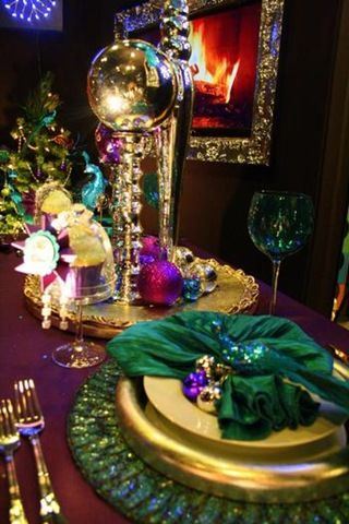 If you prefer holiday glam, this peacock Christmas tablescape certainly has it. A jeweled peacock nestles in the napkin and Christmas balls in gold, purple, burgundy and blue add additional glitter and glimmer.
