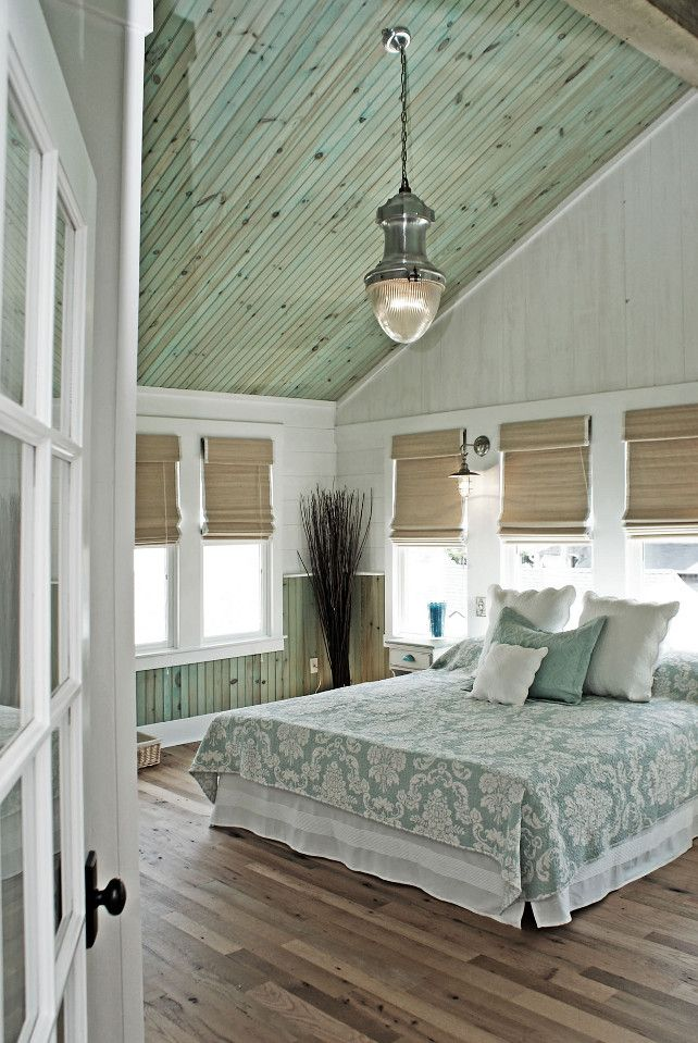 Coastal Aqua Bedroom. The ceiling wood is finished with highly diluted aqua tint to give it just a hint of color and left without varnish to assure the wood looks natural and that there is no reflection. The light fixture is the Vintage Streetlight Prism Pendant from Restoration Hardware. The bed linens are from Manuel Canovas.