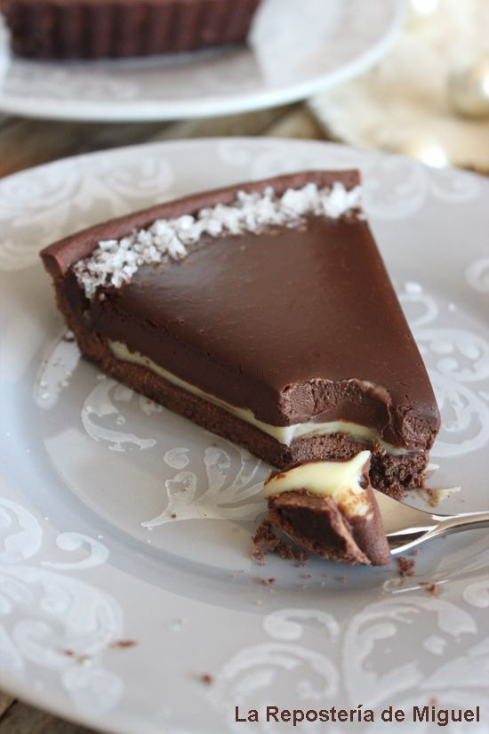 A serving of chocolate cake on a plate That is missing a couple of spoons and and where you can see the different layers of chocolate and sm ...