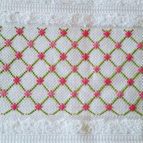 Toalla bordada en punto cruz con  figuras geográfica, rosa y verde: