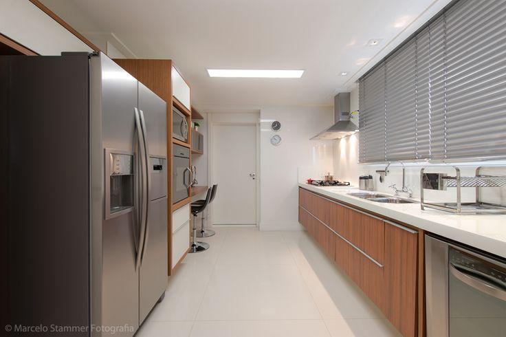 cozinha de apartamento Cozinha com bancada branca + armários de madeira + eletrodomésticos em inox. A bancadinha é de madeira e embutida no mesmo alinhamento dos armários. Projeto Gisele Busmayer, via Stammer. kitchen