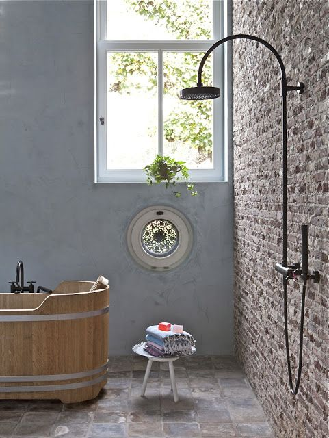 wood tub with a brick wall, and a small window/roster and a small rainshower!