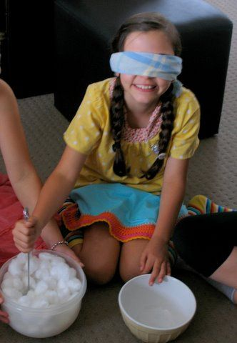 Cotton wool ball game - whoever transfers the most cotton balls with a spoon blindfolded in 30 seconds wins