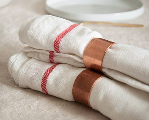 We crafted these snazzy napkin rings using 1.5-inch copper pipe from the hardware store. The pipe was cut down using a miter saw and then its edges were filed with a Dremel. The napkins are from IKEA.