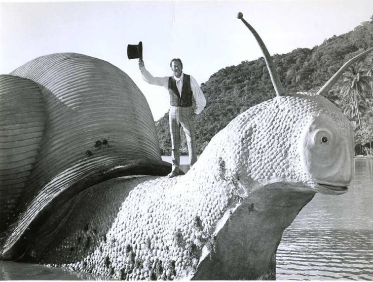 "Dr. Doolittle sailing home on a Giant Pink Sea-Snail. Photo still from ""Doctor Doolittle"" (1967) starring Rex Harrison."