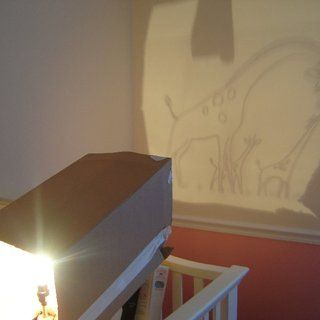 """I made a makeshift projector using a box, a lamp and some tape. Project the transparency onto the wall. I found that using a light bulb without the """"frosting"""" on the inside made for a clearer picture."""