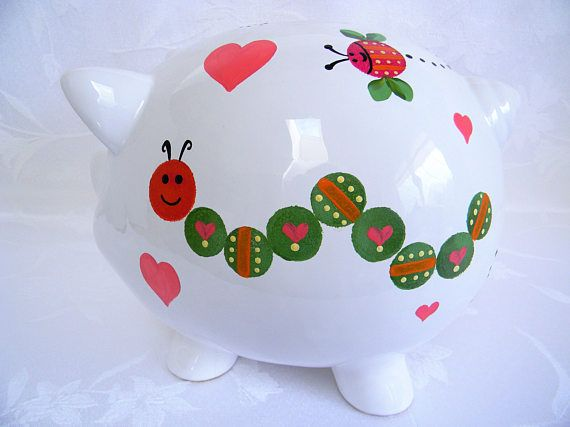 Fun and whimsical caterpillars are hand painted on each side of this large piggy bank. The body is in a medium shade of green with melon hearts, orange stripes and yellow tiny dots. The head it done in a mix of magenta and orange with black details. Flying insects on each side and the back are painted in magenta with two tone green wings and details in yellow, orange and black. There is also a tiny insect on the nose of this piggy bank with black eyes and a pink mouth. This piggy bank can be…