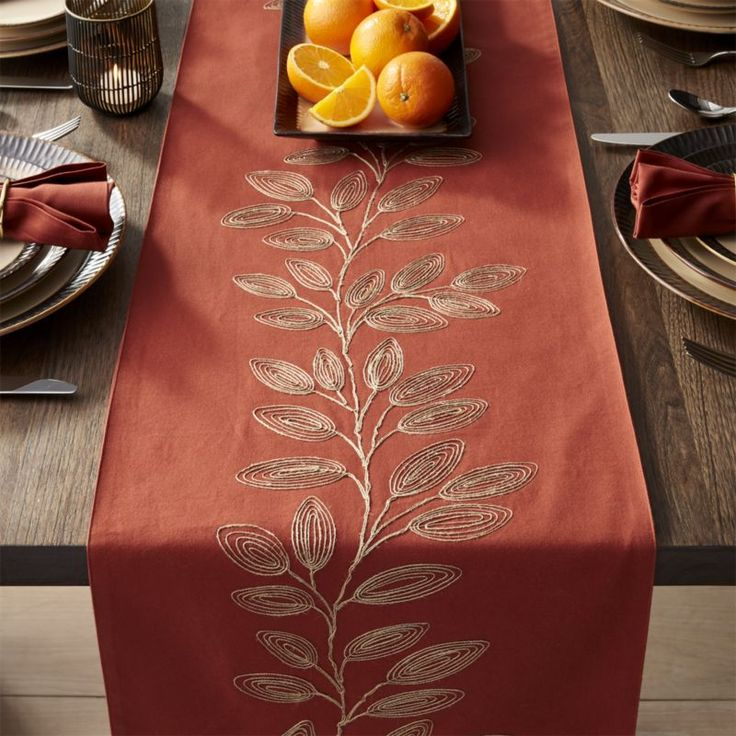 Shop Greer Table Runners. Metallic jute embroidery traces a graphic leaf pattern on barn red cotton in this casual yet elegant table runner. Finished with a solid cotton backing, the runner coordinates with matching placemats.