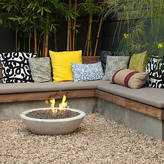 backyard with fire pit and bench seating.