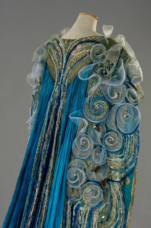 "Costume:Gabriella Pescucci in 1998. ""Queen Titania"". organza is in tones ranging from ivory to teal, with the central panel embroidered chenille yarns, golden threads and green stones.The mantle, with its interior of blue georgette fabric all gold and silver wire, consists on the combination of large edges and silk embroidered inserts with large pleated blue silk drapes. The embroidery, are a variety of materials including: chenille wires, wires gold, azure stones and nylon tulle. Detail:"