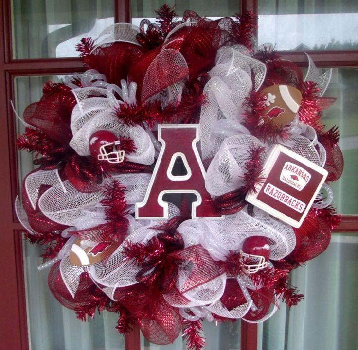 Arkansas Razorback College Football Cardinal Red and White Deco Mesh Door Wreath. This Deco Mesh Arkansas Razorback Fan Wreath is made with deluxe cardinal red and White deco mesh on a cardinal red metallic wreath. The wreath is trimmed with white and cardinal red ribbon and top off with a hand painted A that's sealed for weather protection. The Deco mesh wreath also features 2 Licensed Arkansas Razorback Riddell Football helmets and top off with 2 cute little footballs . Bring your team...