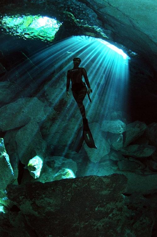 """坂井直樹の""""デザインの深読み"""": 深みかかったブル-の海の中を光のスポットライトが降り注ぐ。そのステ-ジの中を人間が悠々と泳いでいる。ジンベイザメ と泳ぐフリーダイビング世界記録保持者の「二木あい」"""