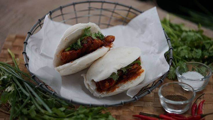 Recipe with video instructions: A Chinese treat you can now make at home. Ingredients: 4 rice buns, olive oil, 1tsp Paprika, 1 tsp wasabi powder, 1 tsp black pepper, 1 tbsp miced ginger, 3 tbsp tomato paste, 1 tbsp brown sugar, 1/2 cup chicken stock, 4 tbsp mirin, 1 tbsp white wine vinegar, 1 tbsp soy sauce, 1 tsp sriracha, 4 Chicken thighs, salt and pepper to taste, 1 red chili, spring onions, 2 lime, coriander