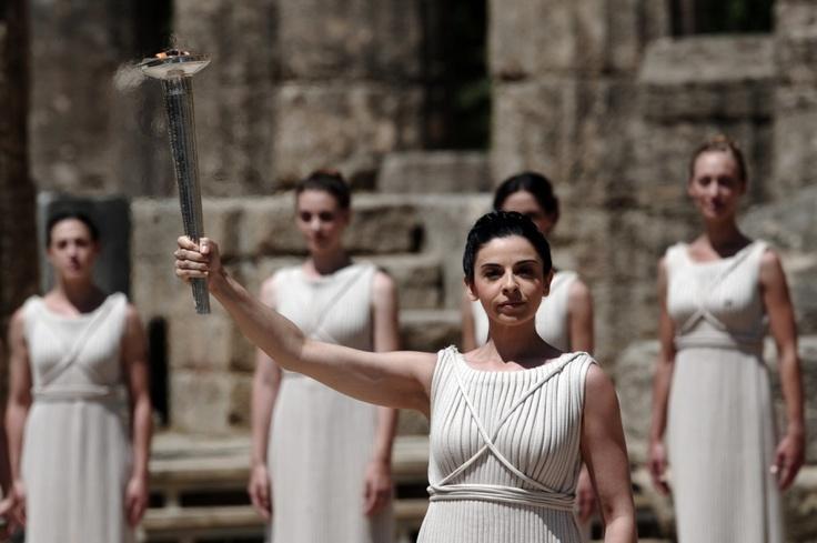 Olympia, Griechenland, 9. Mai 2012:  Im alten Olympia, dem Austragungsort der Olympischen Spiele der Antike, hält die griechische Schauspielerin Ino Menegaki als Hohepriesterin verkleidet das Olympische Feuer, das in einer feierlichen Zeremonie von Darstellern entzündet wurde.