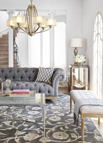 Gray-toned furniture and floor coverings keep the color palette calm, while a graceful chandelier brings in a bit of classic gold.: