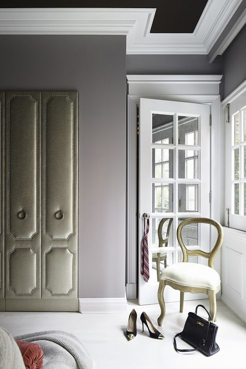 Fabulous closet features chocolate brown ceiling accented with trim moldings over lavender walls framing a gray fabric door with silver nailhead trim disguised as a wardrobe leading into a secret closet beside glass paned door to the master bathroom.