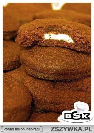 Czekoladowe ciasteczka z niespodzianką w środku Składniki: 140g masła 140g cukru pudru 2 żółtka 255g mąki 30g kakao tabliczka białej czekolady Do miski wrzucamy masło i cukier puder. Ucieramy na gładką masę. Dodajemy żółtka i dokładnie wszystko mieszamy. Następnie dodajemy mąkę i kakao i wyrabiamy ciasto. Wkładamy je na chwilę do lodówki, a w tym czasie nastawiamy piekarnik na 190ºC. Wyciągamy ciasto z lodówki, rozwałkowujemy cienko i wycinamy okrągłe ciasteczka, żeby wyszła ich parzysta…
