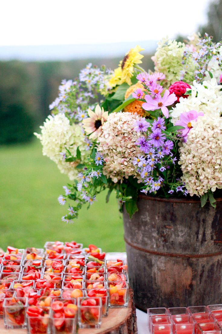 Tomatoes and a bucket of garden flowers made for a wedding,    Photography By / http://katedrewmiller.com