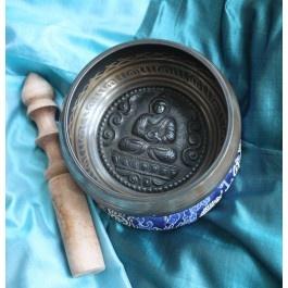 Particolare Campana tibetana di dimensioni medie color bronzo e nero, proveniente dal Nepal, al cui interno emerge a rilievo l'immagine del Buddha nella posizione del loto. Lungo il bordo esterno è riportato un mantra.