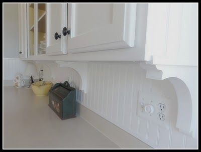 """I think [the corbels] make all the difference. For only sixty-four dollars I was able to create a real designer look. Once installed, I gave the backsplash and corbels two coats of paint to give it a seamless finish.  I trimmed every edge [of the cabinets with beadboard & molding]."" - The Empty Nest via Remodelaholic"