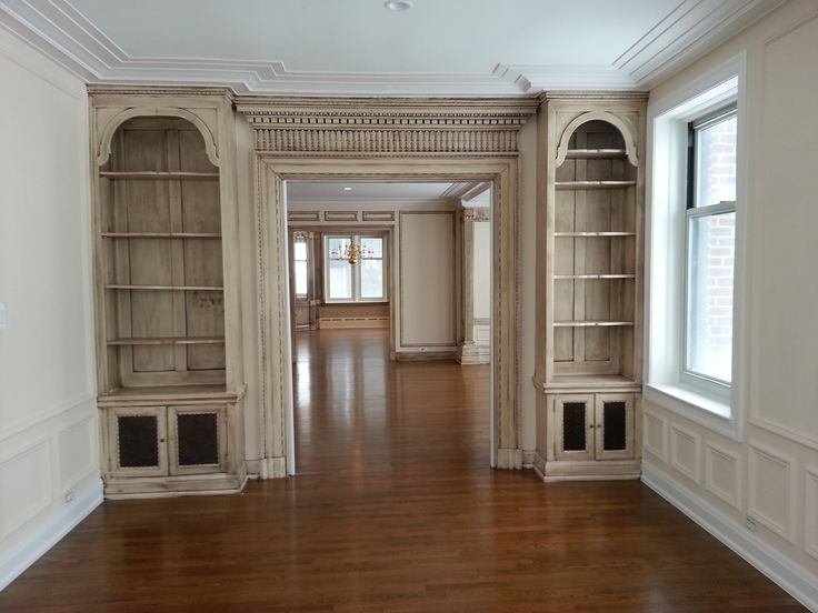 A set of bookcases flanking plaster molding with new wood floors