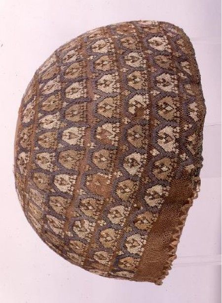 This hair net/cap is bloody brilliant. Western European, dated 1200-1400, 20 cm diameter. Held in Sint-Truiden [district], Limburg, Belgium in the Assumption Church O.L.Vrouw. The underlying net is knotted in red/beige organzizinjde (silk thread?) with  +/- 64 intersections per cm2. The embroidery over it (click through and zoom!) is in grey, white and beige organzinzijde in stopwerk (knotted stitch? Sorry, rubbish at Dutch) over the mesh. Woven cords form loops at edge for tightening cord.