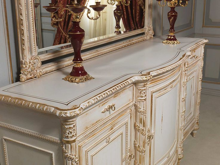 For the classic luxury furniture collection of the White and Gold living area, sideboard and mirror carved in Louis XVI style, finishing white over gold. Carvings realisedby hand by italian artisans