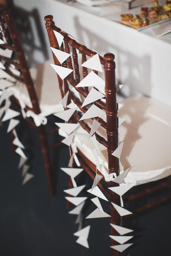 geometric paper garlands for the chair backs, photo by Katie Osgood http://ruffledblog.com/green-building-brooklyn-wedding #garlands #geometric #triangles