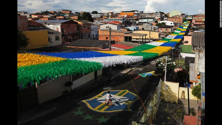 A boy rides his bicycle along a street in Manaus, Brazil, on Saturday, May 17. The street is decorated for the upcoming World Cup soccer tou...