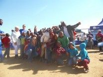 FOUNDER of Under His Covering, Carike Pretorius, squats in front with volunteers and some of the beneficiaries of the soup and bread drive. Photograph supplied