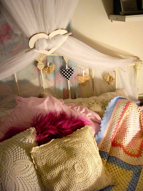 Wooden Heart used to Hold back Mosquito Net. Fabric Heart Bunting on the Head Board.