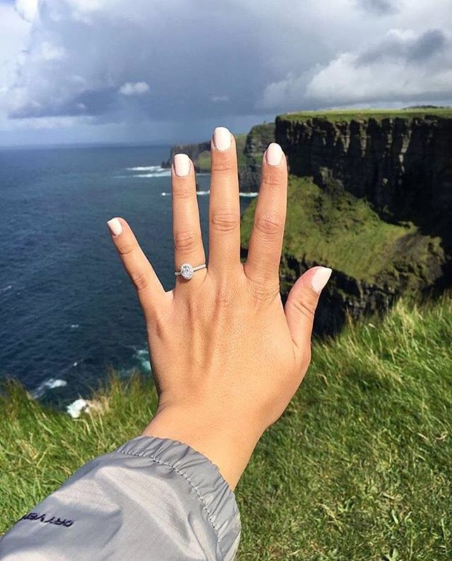Cloudy skies but our pave halo diamond engagement ring still shines  #JamesAllenRings : @emilypool91  : 17307W14 . . . . #engaged #proposal #views #backdrop #greenery #greenlife #grass #rocks #parker #jacket #sea #water #ocean #nature #travel #destination #surpriseproposal #cloudyskies #skiesofinstagram #instagramviews #scenery #vacation #ringselfie #tuesday #tuesdayvibes #manicure #inlovewithmybestfriend #bridetobe