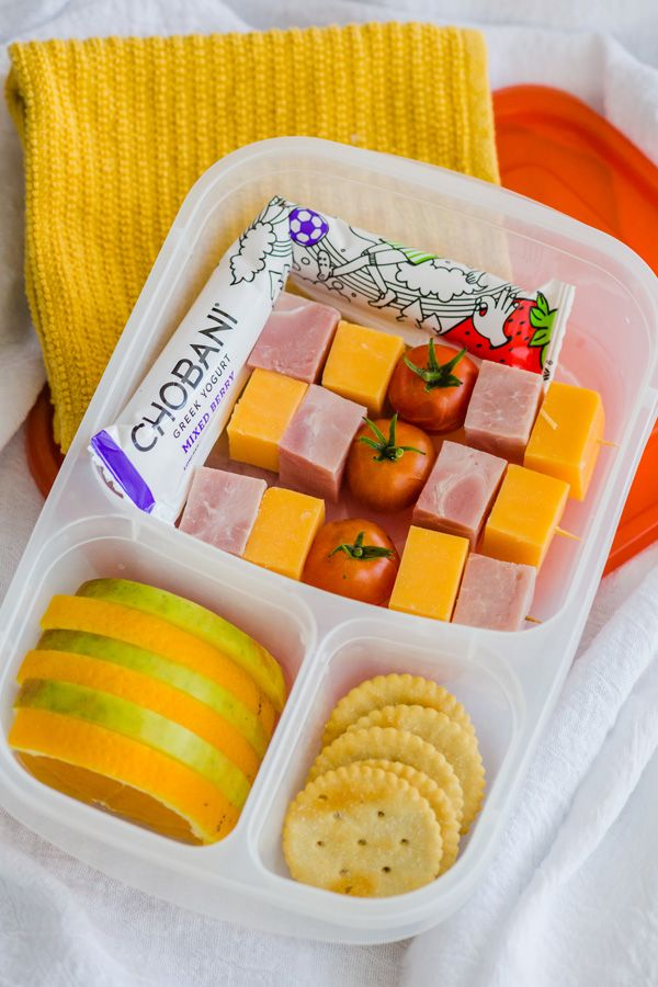 A super protein-packed lunch to keep them going all day long. Ham, cheese and crackers, a garden fresh tomato, with apple and orange slices. This lunch is made even better with Mixed Berry @chobani Greek Yogurt Kids Tubes – with all natural ingredients, 25% less sugar than the leading yogurt tubes, and 5 grams of protein. Quick tip: freeze the yogurt tube bent in the box like this, and it'll help keep the rest of the lunch cool until lunch time. Sponsored by Chobani.