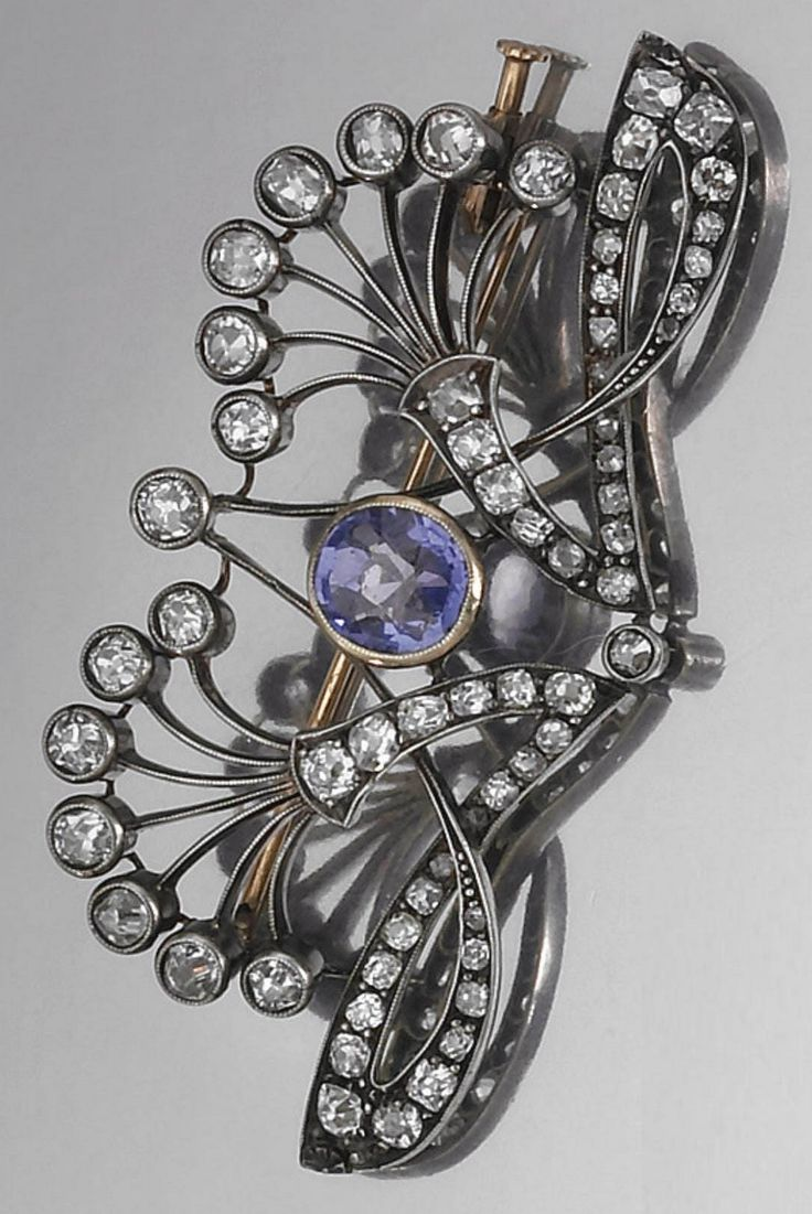 A BELLE EPOQUE GOLD, SILVER, SAPPHIRE AND DIAMOND BROOCH, 1910S. Designed as two stylised cornucopias, set with old-cut diamonds with a circular sapphire at the centre. #BelleÉpoque #brooch