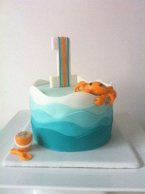 simple and cute beach themed fondant cake with blue and white waves and an orange crab . ocean theme . sand pail and shovel . 1st birthday cake idea