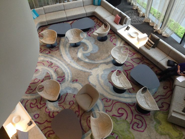Lobby with a creative set of seats that matches perfectly the rug design.
