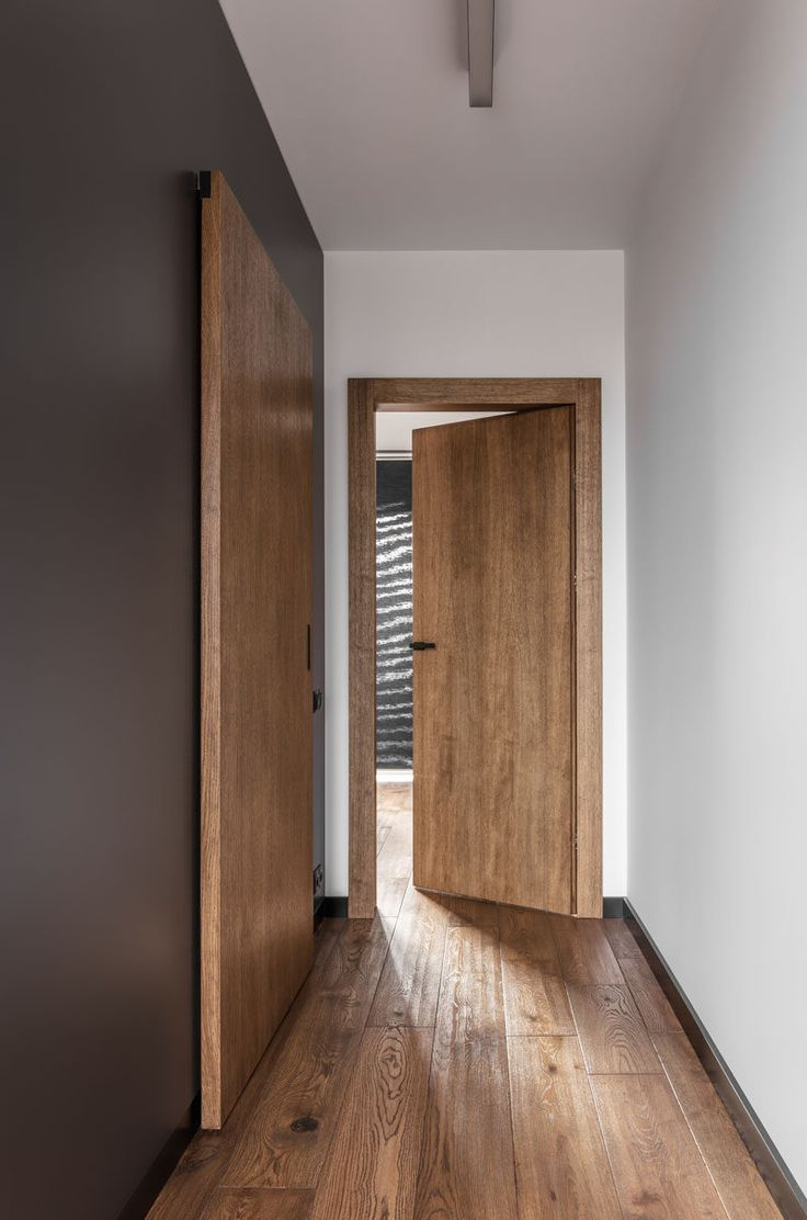 This contemporary apartment features wood doors, dark grey accent walls and wood flooring.