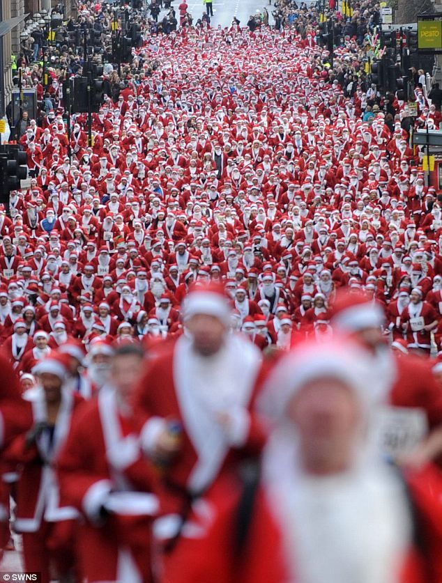 Sea of red: Thousands of people take part in the annual Santa Dash in Glasgow to raise money for charity