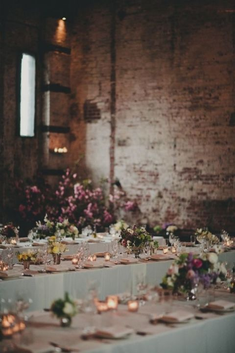 Romantic Industrial Wedding Reception Full Of Candlelight And Purple Flowers