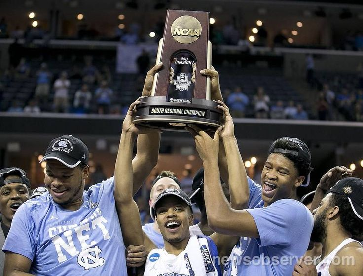 North Carolina's Kennedy Meeks (3), Nate Britt (0) and Isaiah Hicks (4) accept the South Regional championship trophy following their 75-73 victory over Kentucky in the NCAA South Regional Final on Sunday, March 26, 2017 at FedExForum in Memphis, TN.