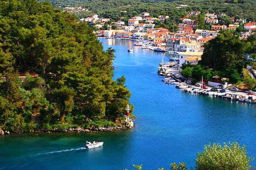 Narrow snaking waterway with housing and boats. Gaios, Paxos island, Ionian Sea