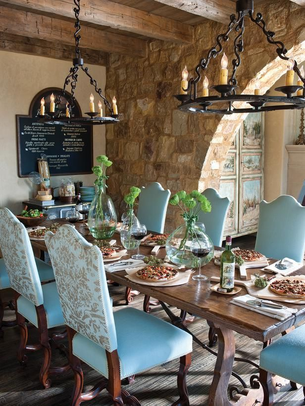 DINING ROOM  Blue padded dining chairs gather around an 18th century table, curved trestle base, and nature'simperfections. A stone archway divides the space
