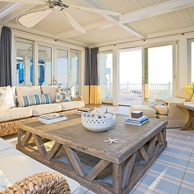In this living room, an oversize coffee table anchors the space and suits its large size; architectural detailing like coffers and a tongue-and-groove ceiling warm up the voluminous room. Framing the glass doors are colorblock draperies; the blue signifies water and sky, the yellow, sand and sun. | Coastalliving.com